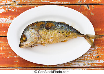Fired thai mackerel on white dish served on table