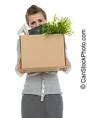 Fired woman employee hiding behind box with personal items