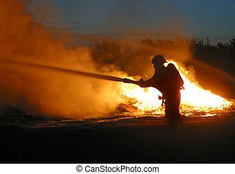 firefighter at work - A lone firefighters battles a blaze.