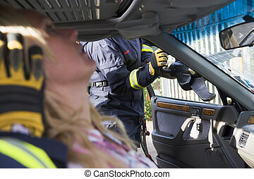 Firefighter cutting out a windshield after an accident with injured woman in foreground (selective focus)