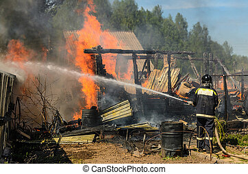 Firefighter extinguishes burning house engulfed in flames using fire hose with water.