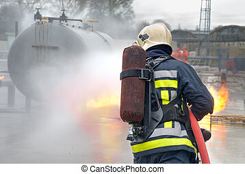 Firefighter in protective clothing, with helmet and oxygen tank extinguishing tank fire with a hose and water jet in an industrial location. Back view.