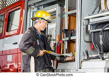 Firefighter Fixing Water Hose In Truck At Fire Station