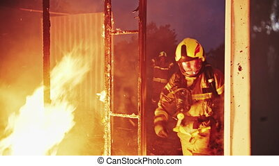 Firefighter helping to extinguish fire in burning house.