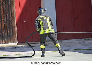 firefighter in action during a fire with the water hose