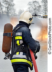 Firefighter in action - Firefighter in protective clothing,...