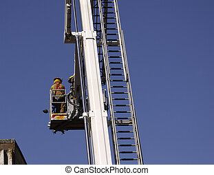firefighter lifted in cherry picker - color photo image of...