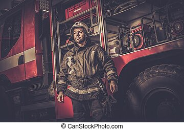 Firefighter near truck with equipment