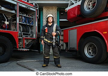Firefighter near truck with equipment with water water hose over shoulder