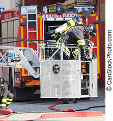 Firefighter on cage of fire ladder