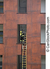 Firefighter on the wooden ladder enters the window