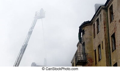 Firefighter on turntable ladder fighting fire on burning...