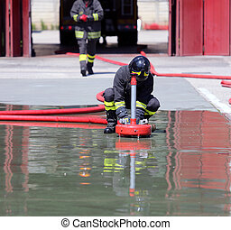Firefighter positions a powerful fire hydrant during the exercises in the Fire Station