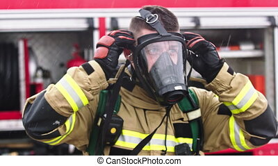 Firefighter removing gas mask from hs face in front of the firetruck. High quality 4k footage