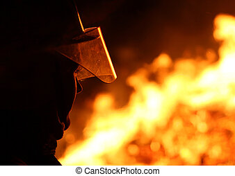 Firefighter - Silhouette of a firefighter facing a blazing...