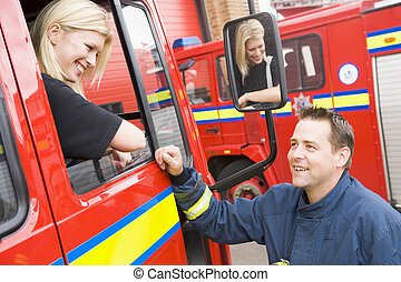 Firefighter sitting in the cab of a fire engine talking to a co-
