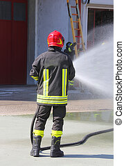 Firefighter sprays water with the spear fighting during the exercise