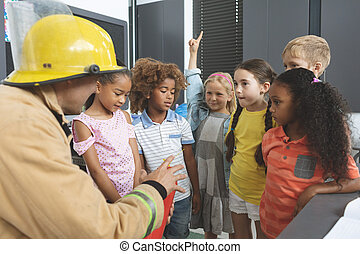 Firefighter teaching about fire extinguisher to school kids in classroom
