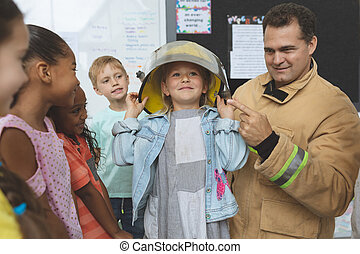 Firefighter teaching fire safety to school kids at school