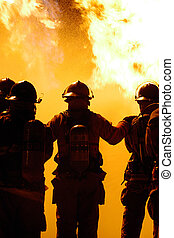 firefighter teamwork - A team of firefighters move in on a...