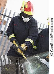 Firefighters breaking a car windscreen to help a car crash victi