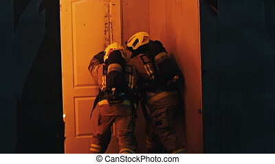 Firefighters breaking into the burning house
