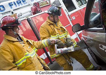 Firefighters cutting open a car to help an injured person
