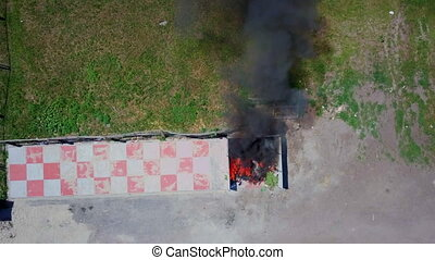 Firefighters extinguish burning garbage can, aerial footage,...