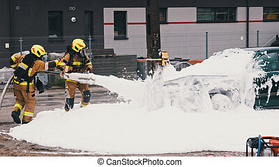 Firefighters extinguish fire from the burning car using foam
