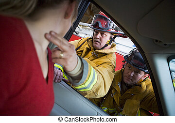 Firefighters helping an injured woman in a car