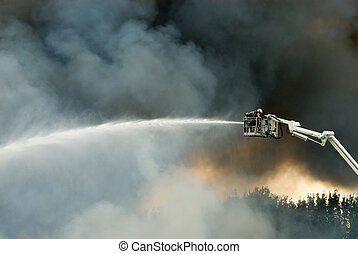 Firefighters in action - a huge fire with firefighters in ...