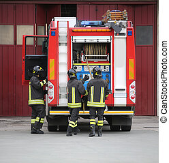 firefighters in action and the fire engine during a fire drill