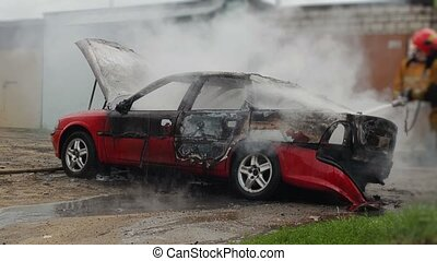 firefighters or firemen extinguish a burning automobile...