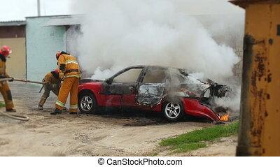 firefighters or firemen extinguish burning passenger car...