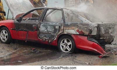 firefighters or firemen pour water on a burnt car, auto was...