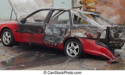 firefighters or firemen pour water on a burnt car - firemen...
