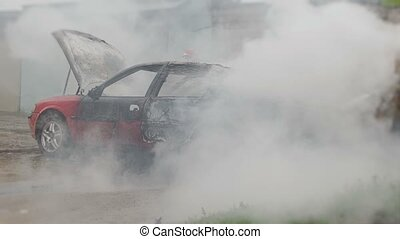 firefighters or firemen with hose extinguish a burning car...