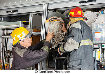 Firefighters Removing Water Hose From Truck - Male ...