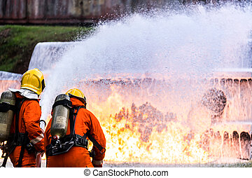 Firefighters spraying down fire flame from oil tanker truck accident