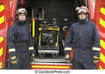Firefighters standing by the equipment in a small fire engine