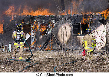 Firefighters standing in front of a burning house - Two...