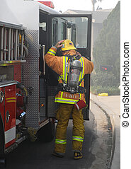 Firefighter puts on his gear to prepare to fight a house fire.