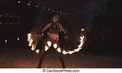 Firegirl performing art of spinning fans at dusk -...