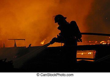 A firefighter is silhouetted by a blaze.