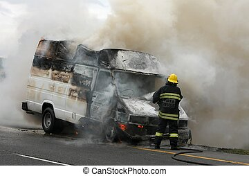 Fireman putting out burning van on the side of the road