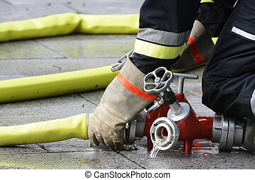 Fireman at work - Hand of a fireman connection a firehose to...