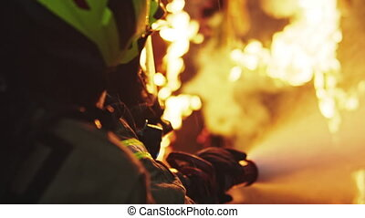Fireman extinguish fire with the hose. Burning house fire drill. High quality 4k footage
