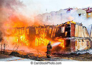 Fireman extinguishes a fire in an old wooden house