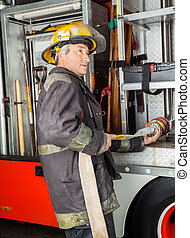 Fireman Fixing Water Hose In Truck At Fire Station