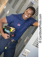 Fireman holding helmet standing by locker in fire station locker room (depth of field)